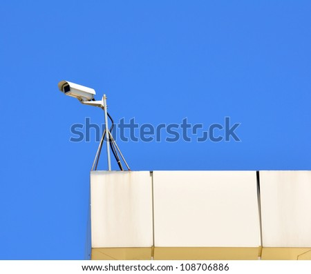 Surveillance cam on a roof watch left - stock photo