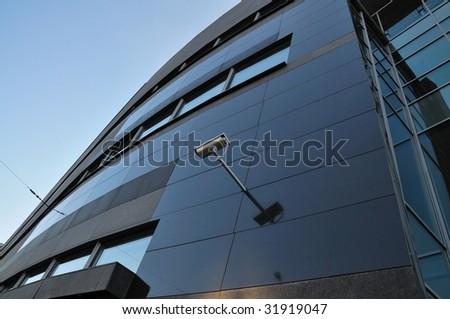 Surveillance camera on glass facade - stock photo