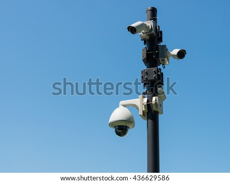 Surveillance cameras on a post on the street against blue sky in Yokohama, Japan. There are several security cameras attached to the pole which cover all directions.