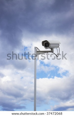Surveillance security camera and cloudy sky as background - stock photo