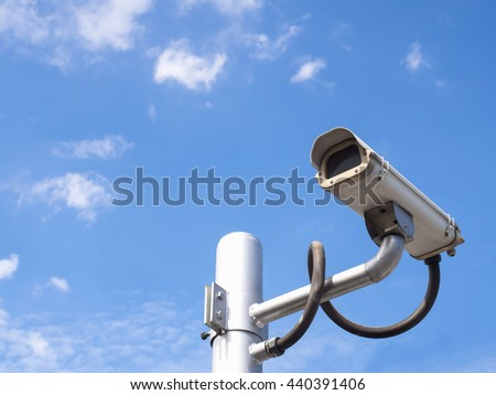 Surveillance Security Camera or CCTV on blue sky background with copy space - stock photo