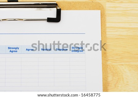 Survey attached to clipboard sitting on table, excellent customer service - stock photo