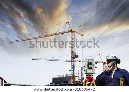 surveying engineer with measuring-instrument inside large construction site - stock photo