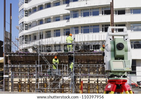 surveying instrument, building workers and scaffolding in the background, engineering surveyor concept - stock photo