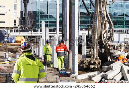 surveyor and building workers with heavy ground machinery - stock photo