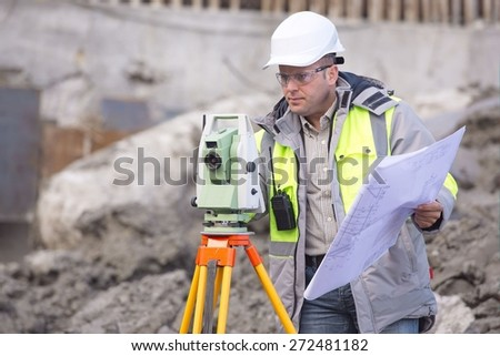 Surveyor at at construction site is inspecting ongoing production according to design drawings. - stock photo