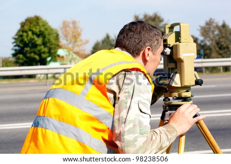 Surveyor engineer making measuring at highway with optical equipment theodolite - stock photo