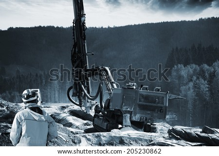 surveyor with drilling machine for dynamiting in rocks and mountains - stock photo