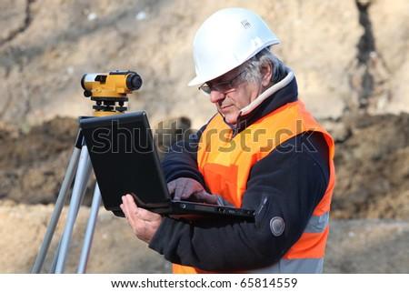 Surveyor with laptop computer - stock photo