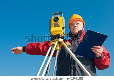 Surveyor worker making measurement in a field with theodolite total station equipment - stock photo