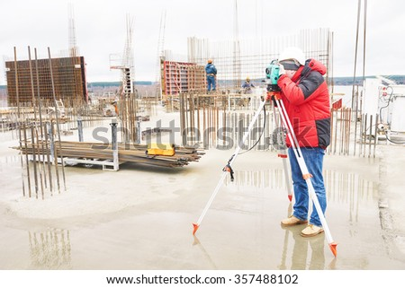 Surveyor working with theodolite transit equipment at construction site - stock photo