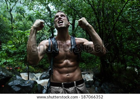 Survival man strong cheering in jungle rainforest. Muscular male survivor celebrating cheerful in forest at night showing muscles and aggressive survival instinct - stock photo