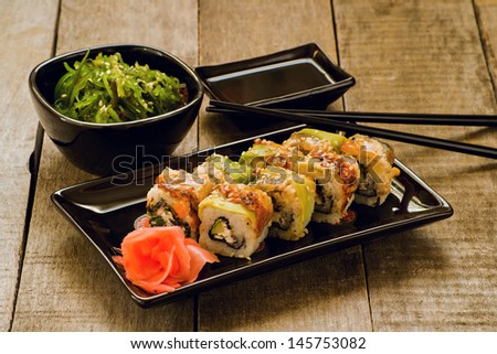 Sushi and chuka seaweed salad with soy sauce on wooden table - stock photo