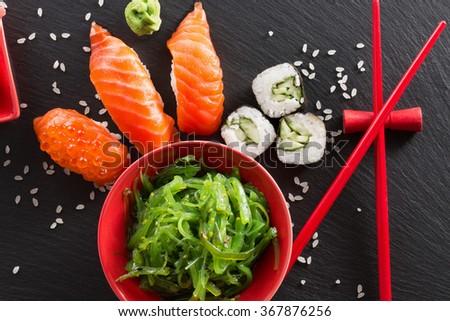sushi and green seaweed salad on a slate table - stock photo