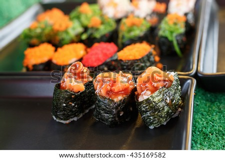 Sushi and sushi rolls served on black  tray at the market, various