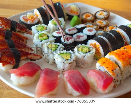 Sushi assortment on a white plate with one pair of wooden chopsticks - stock photo