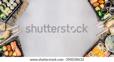 Sushi background with various sushi menu sets: summer rolls,sushi and miso soup in transport boxes with chopsticks on gray stone background, top view, place for text, banner - stock photo