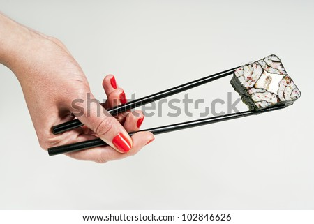 sushi holding in the hand sticks to the background - stock photo