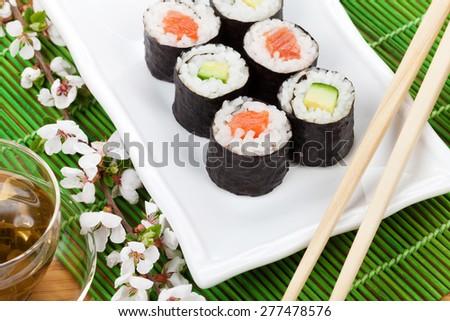Sushi maki set, green tea and sakura branch over bamboo table - stock photo