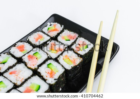Sushi on a black plate with Japanese chopsticks - stock photo