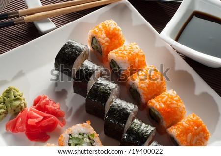 Sushi on a white plate, on a wooden mat