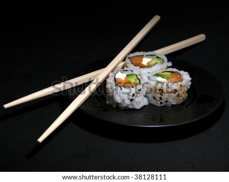 Sushi on black plate with chopsticks - stock photo