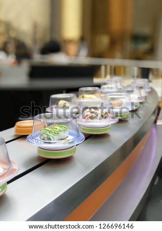 Sushi on conveyor belt in Japanese restaurant - stock photo