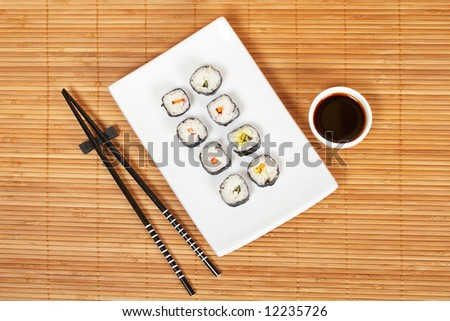 Sushi on the white plate with soy sauce and chopsticks on bamboo mat. Shallow depth of field - stock photo