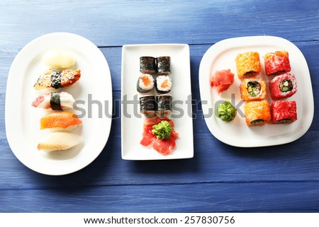 Sushi pieces collection on plates, on wooden background - stock photo