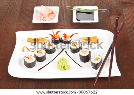 Sushi plate with maki sushi, nigiri sushi, wasabi and chopsticks. Soy sauce and ginger in white bowl. - stock photo