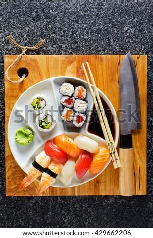 sushi Plate with Sushi Set nigiri and sushi rolls , maki, soy sauce, wasabi, chopsticks - stock photo