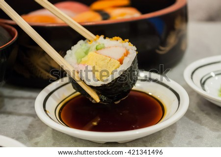 sushi roll in chopsticks close up - stock photo