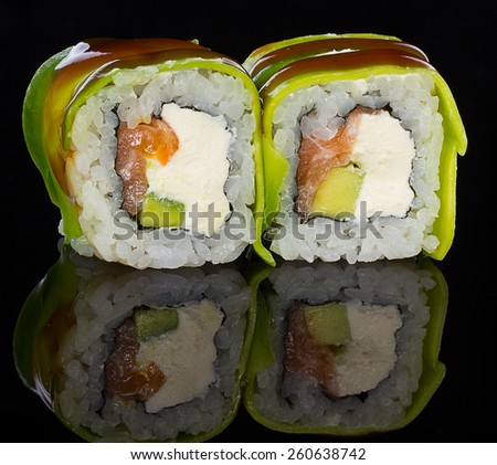 Sushi roll over black background with reflection