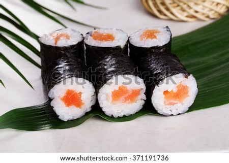 sushi roll salmon chives mini kappa maki in the still life on a tropical leaves, kappamaki