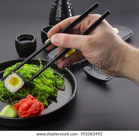 Sushi roll with daikon in chopsticks over black background
