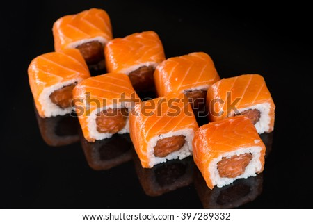 Sushi Roll with salmon over  black background with reflection - stock photo