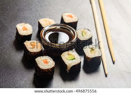 Sushi rolls and sticks on a black surface