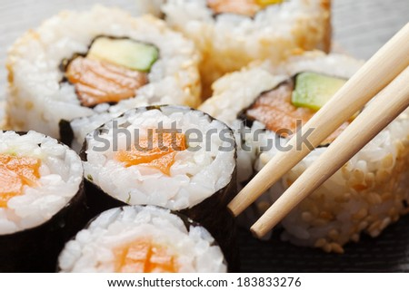 sushi rolls assortment on plate and chopsticks - stock photo