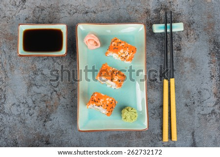 Sushi rolls with masago, served on turquoise plate with pickled ginger, soy sauce and chopsticks. Top view. - stock photo
