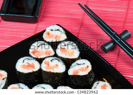 Sushi rolls with salmon and tomato on a black square plate