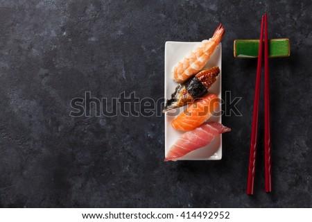 Sushi set and chopsticks on stone table. Top view with copy space. Unagi, ebi , tuna and salmon - stock photo