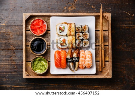 Sushi Set nigiri and rolls with chopsticks, ginger, soy sauce and wasabi in tray on rustic wooden background - stock photo