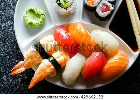 Sushi Set nigiri and sushi rolls served on black marble slat - stock photo