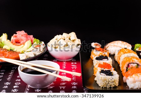 Sushi set served on a plate, soy cheese, lime on black background - stock photo