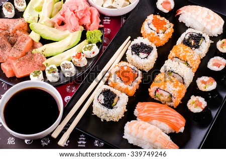 Sushi set, soy sauce, ginger, wasabi, black and red roe, avocado, salmon, cheese on black background