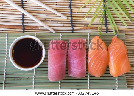 Sushi set with chopsticks and sauce on bamboo table - stock photo