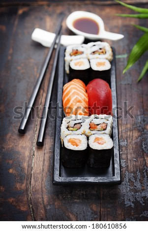 sushi with chopsticks on wooden background - stock photo