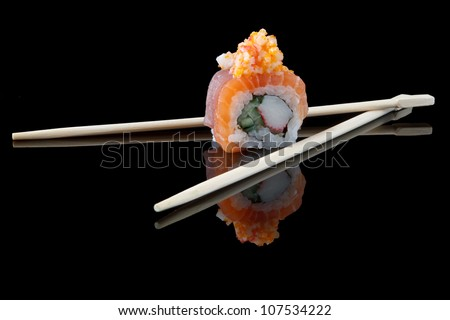 sushi with chopsticks over black background - stock photo