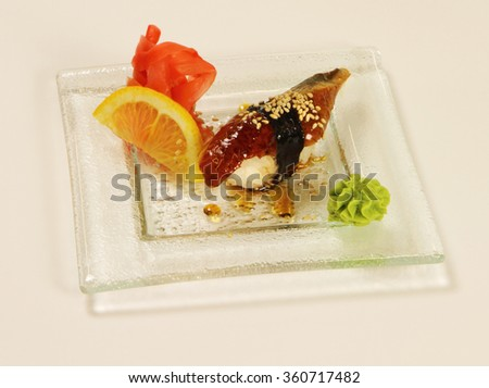 sushi with fish, lemon, ginger and wasabi sauce on a white plate