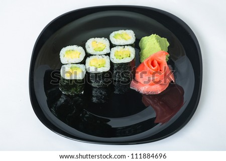 Sushi with ginger and wasabi on a black plate. - stock photo